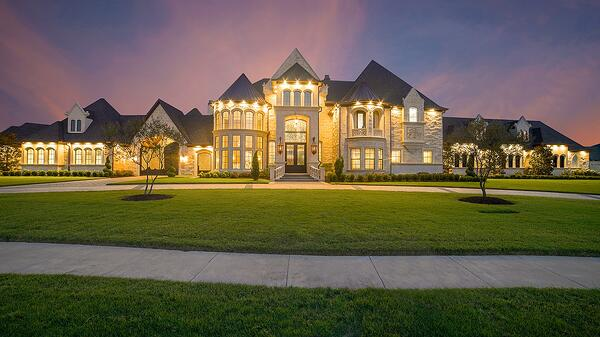 Beautifully lit exterior of a luxury mansion